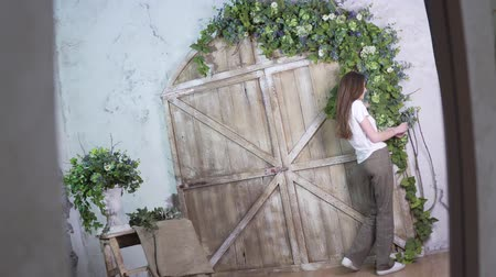 decorador : Shoot in reflection, stylish girl florist decorates a beautiful wooden photo zone with flowers