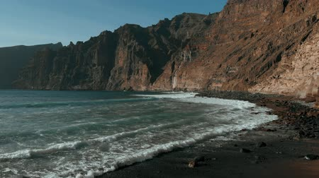 magasság : The most beautiful aerial view: a girl with a hat and a dress runs along the black beach, after which a view of the Los Gigantes, Tenerife, Canary islands, Spain Stock mozgókép