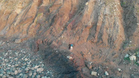 akik : Aerial shoot. The camera moves away from the man and woman who stand at the bottom of the huge rocks. Benijo, Tenerife, Spain