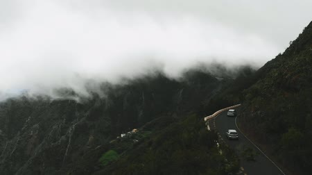 yılantaşı : Birds-eye view - cars are driving on a wet and dangerous road, dense and thick clouds fly over them very low. You can touch the clouds with your hand.