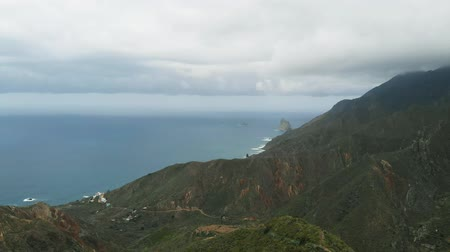 horská pastvina : Aerial view. A single man stands on the edge of a mountain, looking at a beautiful view - the long coast of the Atlantic Ocean, the green valley and the mountains of the Anaga National Park, Tenerife Dostupné videozáznamy
