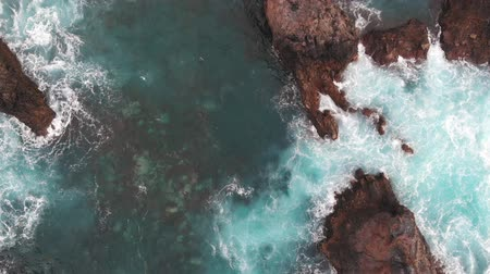 tło : Cinematic shot - drone rises over the coast of the Atlantic Ocean, Tenerife, Spain. Rock in crystal clear water washed by ocean foam