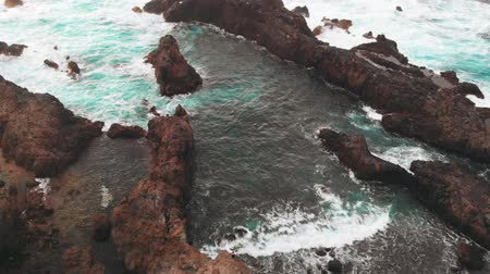 origin : Aerial view from afar - a person stands on the edge of a rock of volcanic origin, the ocean coast. Tenerife, Spain