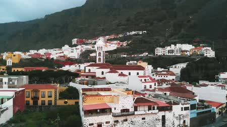 плотно : Aerial view - a cozy little Spanish town, spread out at the foot of the mountains. National architecture, light-colored buildings, Garachico, Tenerife, Spain.