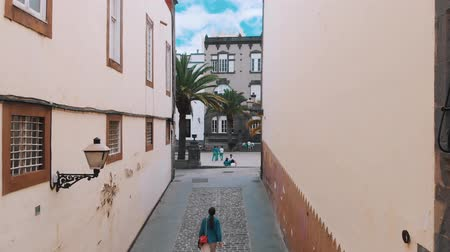 kanarya : Las Palmas de Gran Canaria, Spain - April 23, 2019: Aerial view - young stylish girl walking along a narrow street of the old Spanish city, top view. Stok Video