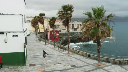 ветреный : AERIAL. Cinematic shot - a girl walks through a deserted Spanish city, along the coast, during a strong wind, in overcast weather, a birds-eye view. Siesta, Gran Canaria, Spain