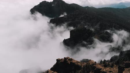origin : Aerial view - beautiful clouds curl in the gorges of the mountains, view from a high altitude of the valley of volcanic origin, Pico de las Nieves, Gran Canaria
