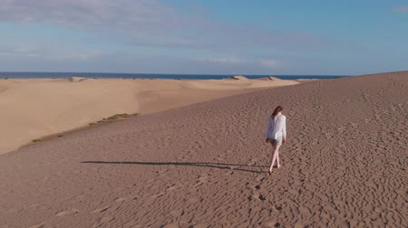 área de deserto : Aerial view - a lonely girl walks and then runs through the desert, Maspalomas, Gran Canaria Vídeos