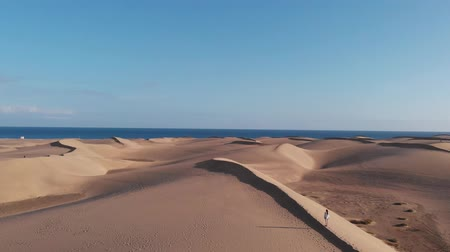 área de deserto : Cinematic shot - slim girl stands on the dune, in the desert, aerial view, Maspalomas, Gran Canaria