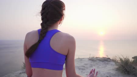 meditando : Cliff Yoga with Sea View - calm and peaceful girl meditates in lotus position, concentrates on breathing.