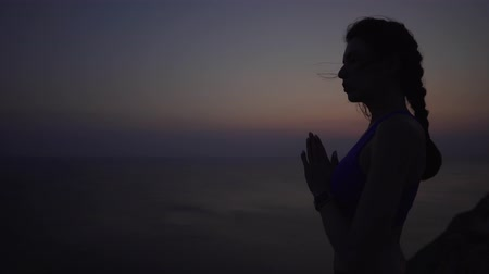 meditál : Calm and girl practices yoga and meditates at sunset by the sea, on a cliff. Athletic woman holds hands together as in prayer. Spirituality, mindfulness and the concept of a healthy lifestyle. Stock mozgókép