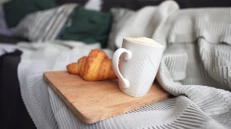 клетчатый : Coffee in a white cup and a fresh croissant on a cozy sofa. Breakfast on a cold winter day. The concept of comfort, warmth and care