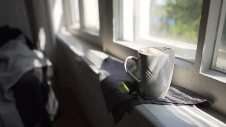 umutlu : Lagom or Hygge concept - white cup of hot coffee on a windowsill in the sun