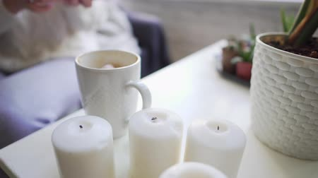 happy socks : Hygge - candles and coffee mug close-up on a white table. Girl adds marshmallows to a hot drink to keep warm and enjoy the taste.