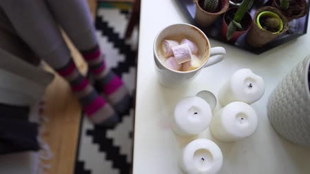 носок : Hygge or Lagom concept - candles, coffee, warm socks on a beautiful carpet on a wooden floor. Young woman adds marshmallows to fresh coffee Стоковые видеозаписи