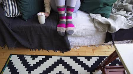 escandinavo : Legs of a girl on a sofa in warm multi-colored socks on a cold winter day in a Scandinavian interior. Hygge philosophy, the joy of home comfort Vídeos