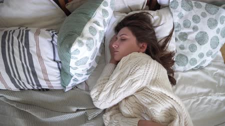 sonolento : Young attractive woman in a white sweater lies on a bed, dreams and goes to bed Stock Footage
