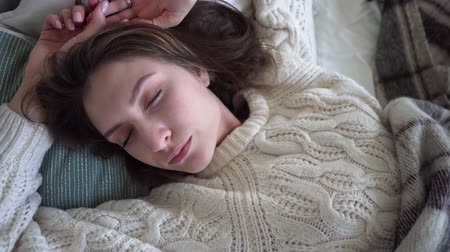 uykulu : Top view of a sleeping girl in a white sweater, coziness and comfort Stok Video