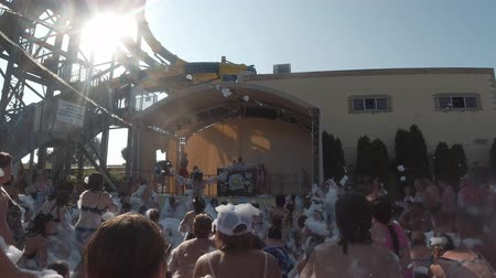 hapiness : Anapa, Russia - August 17, 2019: the crowd at the foam party bounces, water and foam spray, people dance. Slowmo, entertainment and vacation