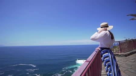 observation deck : Beautiful girl in a stylish hat on the edge of a cliff looking at the Atlantic Ocean. Canary Islands, Spain Stock Footage