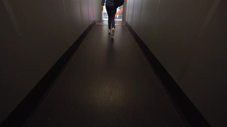 proceed : A young woman walks on a dark gangway after a plane lands. Start a vacation trip. Girl with a backpack in jeans clothes in a narrow corridor Stock Footage