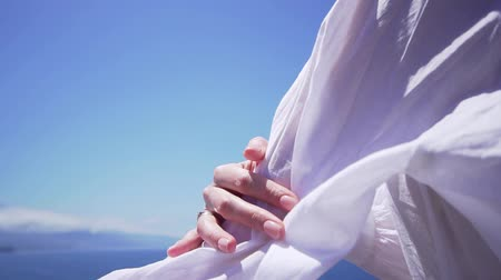 observation deck : Beautiful woman holds her hand on a white shirt on a windy day, slow motion. Girl model on vacation Stock Footage