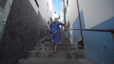 keşfetmek : Stylish woman runs up the stairs in a very narrow street in the old Spanish city. A tourist walks around the city of El Pris, Tenerife, Spain Stok Video