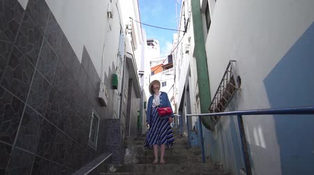 descobrir : A beautiful woman stands in a narrow street between Spanish houses. Tourist on the street of a colorful European city off the coast of the ocean
