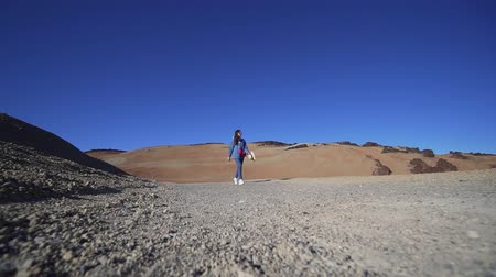 backpacken : Hipster woman walks past the camera through the volcano, desert nature, arid climate. Static shot, wide angle. Inspirational tourism