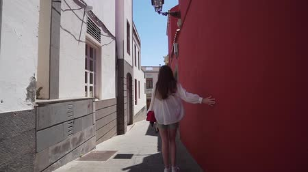 招待状 : A woman on vacation explores the ancient and authentic narrow streets of a European city. Happy girl tourist, rear view.
