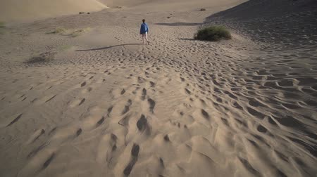 bescheiden : A lonely young woman walks through the dry desert in the arid summer