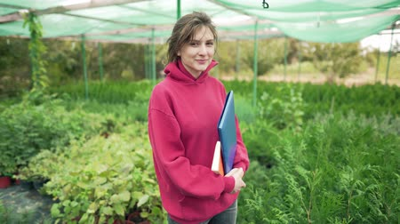 virágárus : A businesswoman with a folder in her hands is smiling and looking at the camera. Portrait of a successful business owner. Local nursery for growing seedlings. Greenhouse outdoor, female seller Stock mozgókép