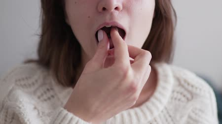 sedative : A young woman puts a sedative pill in her mouth and drinks it with a glass of water. Probiotic and mineral tablet, a useful medicine for maintaining immunity in the disease season, close-up Stock Footage