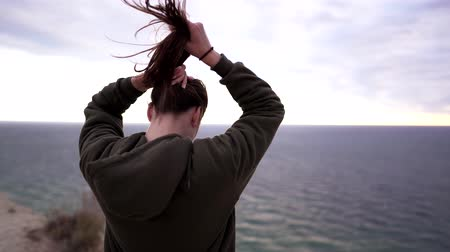 йога : A beautiful young woman athlete walks to the edge of a cliff on a windy day. Sports sweatshirt, strong wind disheveles the girls long hair Стоковые видеозаписи