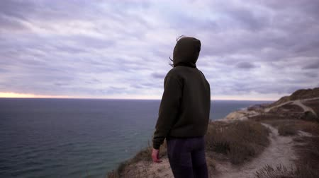montanhas rochosas : Healthy lifestyle. A beautiful caucasian woman in a sweatshirt and leggings stands on the edge of a cliff after finishing a workout. The concept of freedom and tranquility in nature Stock Footage