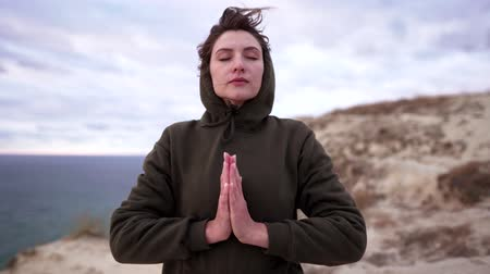koncentracja : Namaste or prayer. Active lifestyle - a calm woman in a sweatshirt holds her palms together. Cliff over the ocean in windy weather
