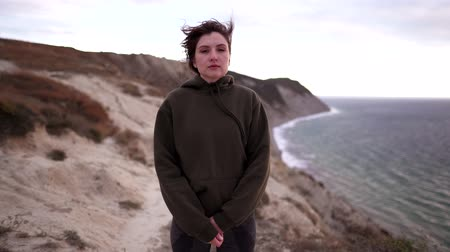 йога : Portrait of an attractive female athlete in nature. Calm young woman in a sweatshirt looks at the camera, strong wind on a cliff above the ocean