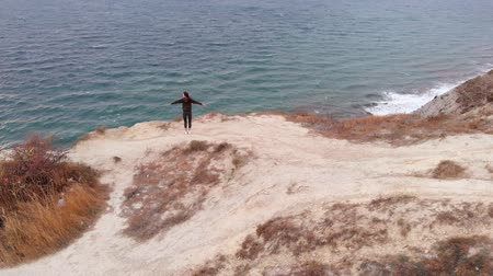 meditacion : Contemplating the environment, a young woman stands on the edge of a cliff above the ocean and practices yoga. Asana, energy and meditation