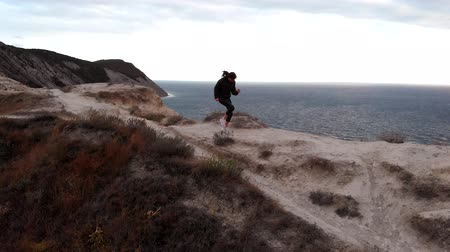 koncentracja : Unmanned view of a woman in sportswear running in one place. Wellness on the cliff, drone view