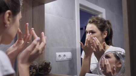расслаиваться : Foam for cleaning the face - a girl with clean skin foaming the cream and applies it on the face, looking in reflection in the bathroom mirror. Facial cleansing, hygiene and skin care Стоковые видеозаписи