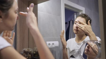 лицевой : Facial, skin cleansing after a working day. Happy caucasian woman applying scrub on face skin in shower room