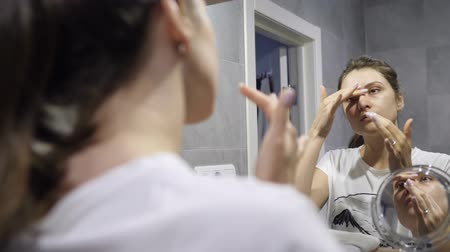 расслаиваться : Face cleansing. Young woman with beautiful skin is engaged in facial hygiene - cleans pores with foam