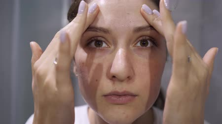 yanak : Facial treatment with foam for washing, a pretty girl looking at the camera. Closeup woman portrait in the bathroom. Freshness, cosmetics and wellness Stok Video