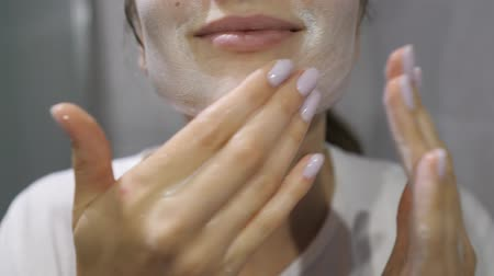 fürdés : Healthy girl with beautiful skin applies a white foam for washing her face close up
