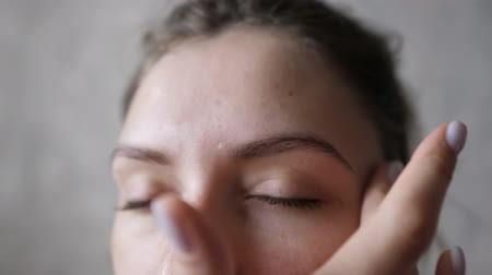 procedimento : Cosmetology procedure - the use of eco serum to restore and moisturize the skin. Close-up of a girl applying cream on her forehead