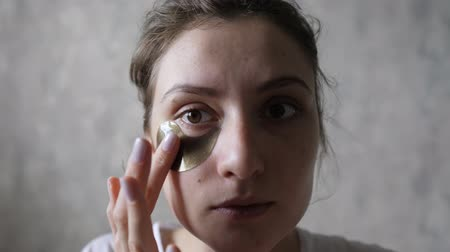masaj : Beauty and care. Portrait of a young woman with perfect skin applying a repair patch under the eyes. Looking at the camera
