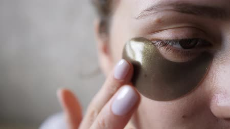 folt : Applying a patch under the eye of a young woman close-up. Beauty and health, swollen skin under the eyes after a sleepless night