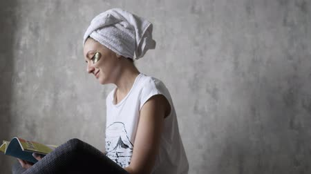 zmarszczki : Relaxation at home - a young woman in a towel and with eye patches reads a magazine. Wellness lifting, beauty treatments