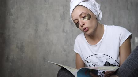 zmarszczki : Woman portrait in the house. Skin care and moisturizing a swollen face. Caucasian girl relaxes in the early morning and reads a journal Wideo