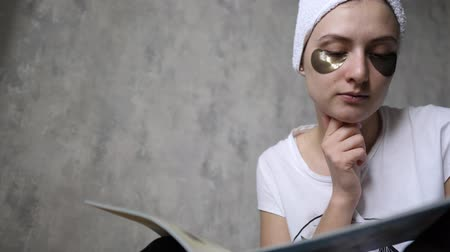 procedimento : Skin care, patches under the eyes of a young woman. Girl reading a magazine at home in a towel. Lifting and wellness cosmetology procedure Stock Footage